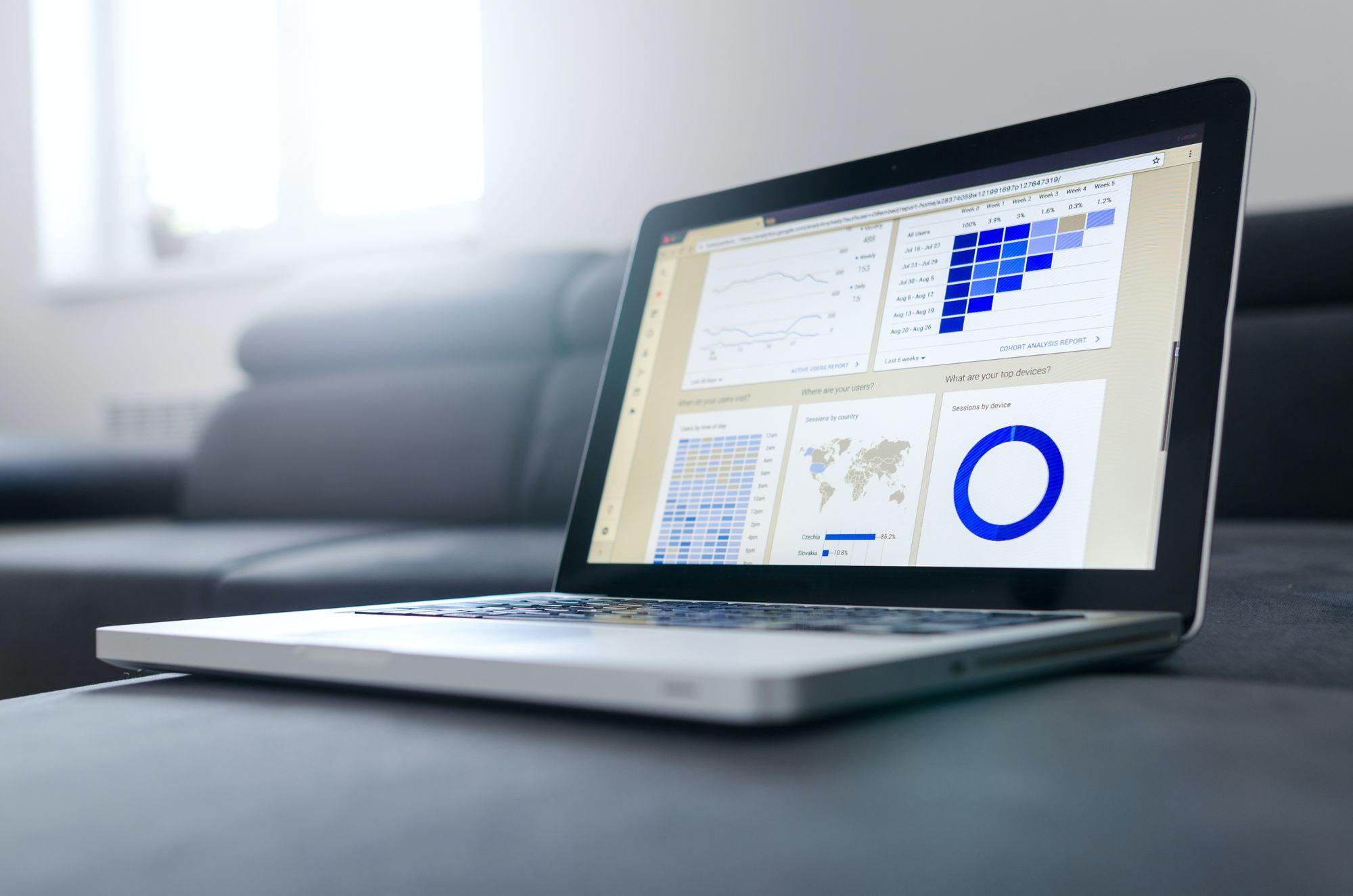 laptop sobre uma mesa exibe dashboards com diferentes dados