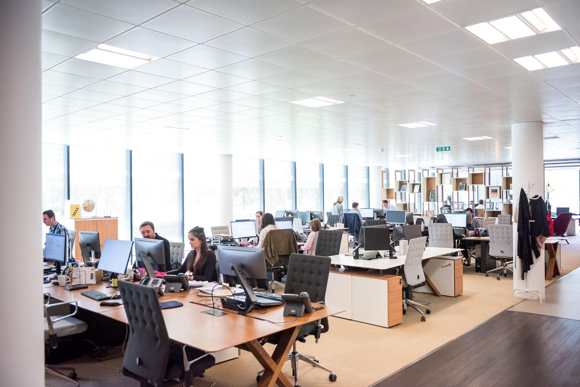 sala de trabalho mostra diversos profissionais trabalhando diante de seus computadores
